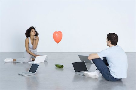 female silhouettes heart - Man and woman seated with laptops, woman blowing man a kiss, bottle and heart balloon between them Stock Photo - Premium Royalty-Free, Code: 695-03390287