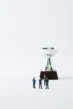 Miniature businessmen standing face to face in front of trophy Stock Photo - Premium Royalty-Free, Code: 695-03390414