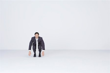 Businessman squatting, dangling arms Stock Photo - Premium Royalty-Free, Code: 695-03390536
