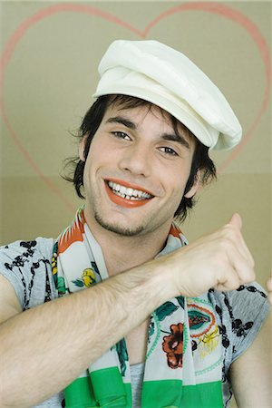 Young man wearing lipstick, cap, and scarf, smiling at camera, portrait Stock Photo - Premium Royalty-Free, Code: 696-03394596