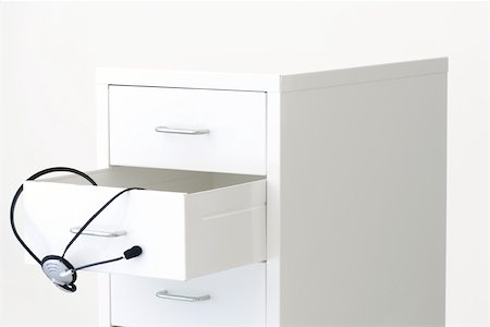 Headset hanging from an open drawer of a filing cabinet Stock Photo - Premium Royalty-Free, Code: 696-03396052