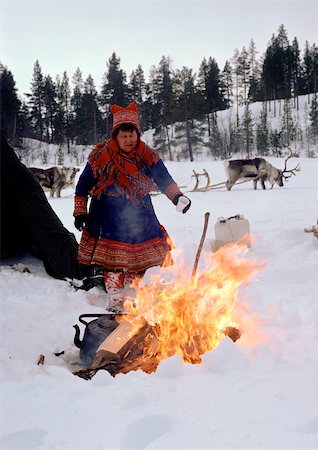 Finland, Saami woman standing next to fire, sled reindeer in background Stock Photo - Premium Royalty-Free, Code: 696-03397259