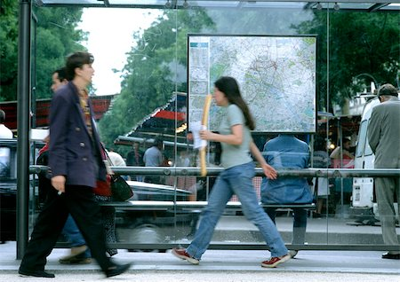 People walking past bus stop, blurred. Stock Photo - Premium Royalty-Free, Code: 696-03397334