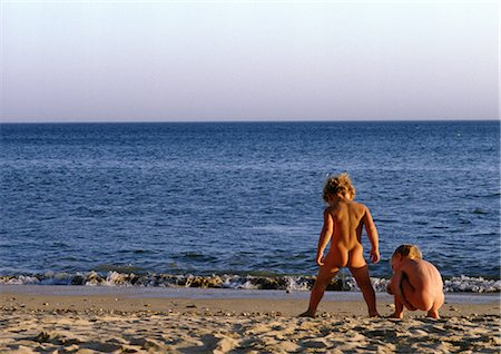 Nude children playing on beach, rear view Stock Photo - Premium Royalty-Free, Code: 696-03397544
