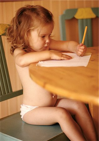 Little girl in underwear sitting at table, drawing Stock Photo - Premium Royalty-Free, Code: 696-03398691