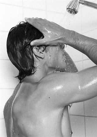 Man taking shower, side view, b&w Stock Photo - Premium Royalty-Free, Code: 696-03399332