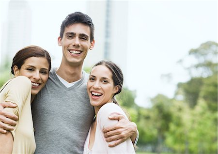 Young man standing with arms around two young women in urban park Stock Photo - Premium Royalty-Free, Code: 696-03400185