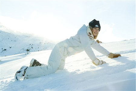 Teenage girl down on all fours in snow, smiling at camera Stock Photo - Premium Royalty-Free, Code: 696-03401772