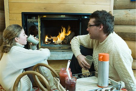 sweater and fireplace - Young man and teenage girl sitting by fireplace, drinking hot beverages, looking at each other Stock Photo - Premium Royalty-Free, Code: 696-03401813