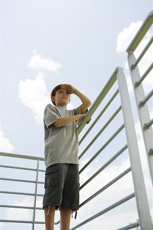 Boy standing on balcony shading eyes, looking at view Stock Photo - Premium Royalty-Free, Code: 696-03402081