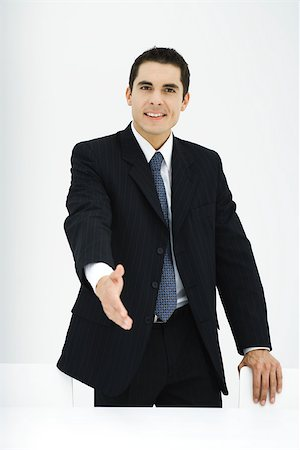 Businessman extending hand toward camera, smiling Stock Photo - Premium Royalty-Free, Code: 696-03402411