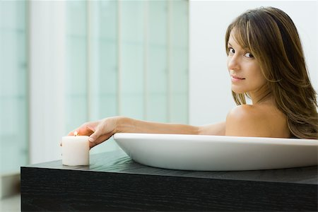 Woman sitting in bathtub, holding lit candle, smiling over shoulder at camera Stock Photo - Premium Royalty-Free, Code: 696-03402439