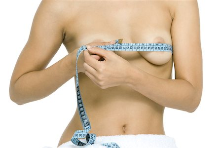 Nude woman wrapping measuring tape around breasts, cropped view Stock Photo - Premium Royalty-Free, Code: 696-03402540