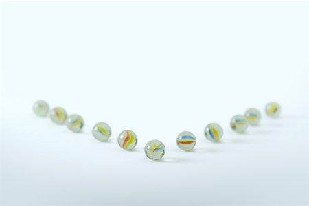Marbles arranged to resemble arrow Stock Photo - Premium Royalty-Free, Code: 696-03402888