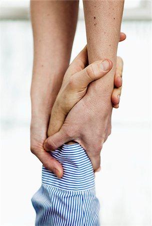 Woman grasping man's wrist, close-up Stock Photo - Premium Royalty-Free, Code: 698-05956030