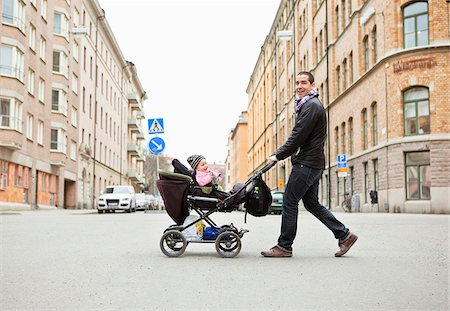 Smiling father walking with cute baby (0-11 months) in stroller Stock Photo - Premium Royalty-Free, Code: 698-05956102