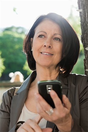 Close-up of woman holding mobile phone and lost in thoughts Stock Photo - Premium Royalty-Free, Code: 698-05957142