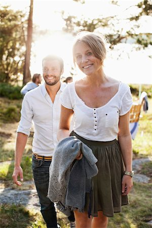 summer - Woman standing with man and friends in background Stock Photo - Premium Royalty-Free, Code: 698-05980307