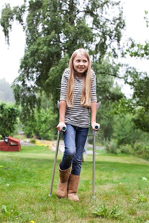Physically impaired girl with crutches looking away Stock Photo - Premium Royalty-Free, Code: 698-05980565