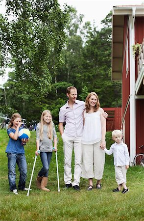 Family with three children standing in back yard Stock Photo - Premium Royalty-Free, Code: 698-05980566