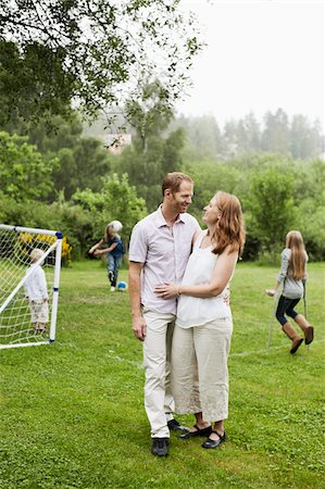 Couple looking at each other with children playing in background Stock Photo - Premium Royalty-Free, Code: 698-05980568