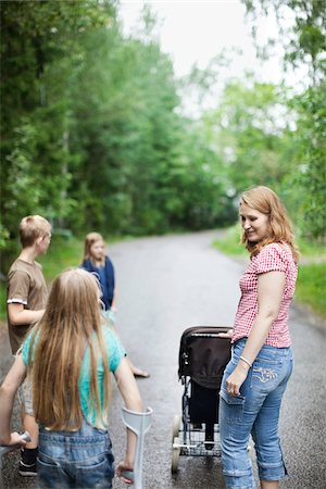Mother with three children walking on road in forest Stock Photo - Premium Royalty-Free, Code: 698-05980592