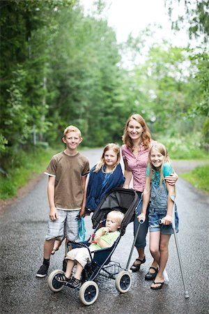 Portrait of mother with children standing on road in forest Stock Photo - Premium Royalty-Free, Code: 698-05980593