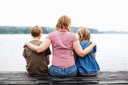 Rear view of mother with arm around her children sitting on pier Stock Photo - Premium Royalty-Free, Code: 698-05980603