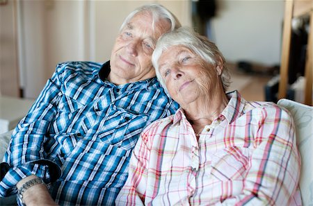 Senior couple relaxing together on sofa in living Stock Photo - Premium Royalty-Free, Code: 698-05980634