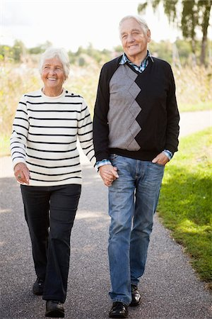 Front view of senior couple holding hands walking in park Stock Photo - Premium Royalty-Free, Code: 698-05980659