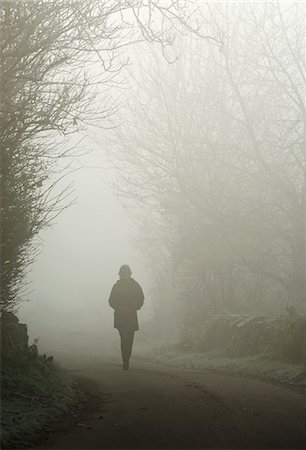 fog (weather) - Person walking on a foggy country road Stock Photo - Premium Royalty-Free, Code: 698-06116954