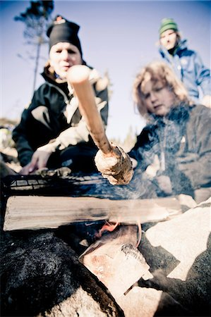 Close-up of young girl holding stick while cooking at camping site Stock Photo - Premium Royalty-Free, Code: 698-06117008