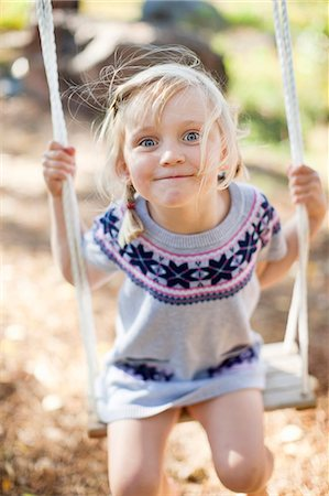 swing (sports) - Portrait of small girl on rope swing in back yard Stock Photo - Premium Royalty-Free, Code: 698-06117067