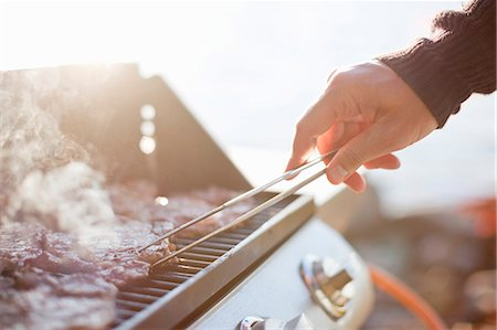 Close-up of man flipping beef with tongs on barbecue grill Stock Photo - Premium Royalty-Free, Code: 698-06117083
