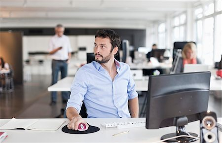 Businessman using computer while looking away Stock Photo - Premium Royalty-Free, Code: 698-06117136