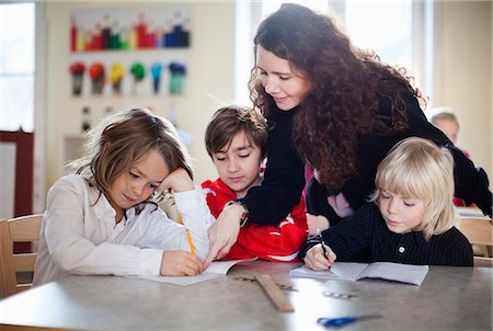 elementary school - Smiling teacher helping students in classroom Stock Photo - Premium Royalty-Free, Code: 698-06117258