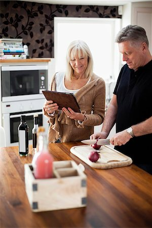 Couple in kitchen using digital tablet for recipe and cooking meal Stock Photo - Premium Royalty-Free, Code: 698-06117283