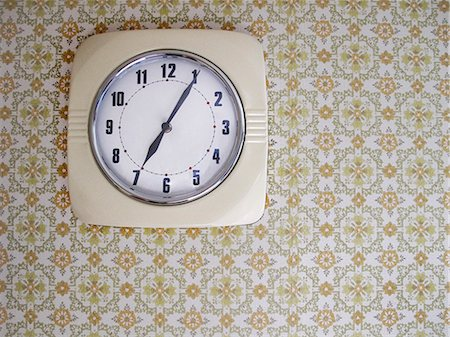 Clock hanging on wallpaper Stock Photo - Premium Royalty-Free, Code: 698-06117384