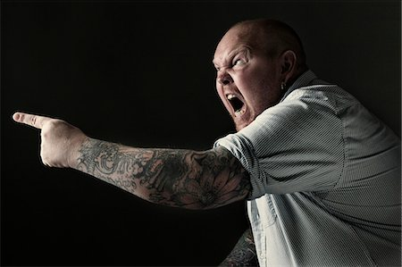 Side view of a furious mature man shouting while pointing over black background Stock Photo - Premium Royalty-Free, Code: 698-06117383