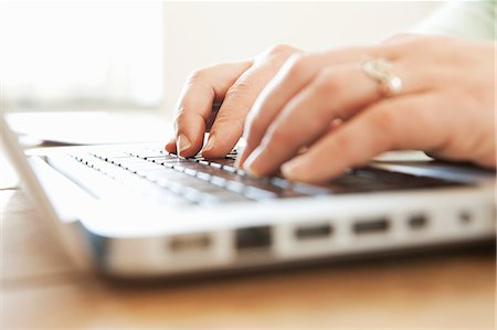 ring hand woman - Close-up of human hand typing on laptop Stock Photo - Premium Royalty-Free, Code: 698-06374593