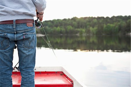 fishing - Midsection of a young man fishing in river while standing on boat Stock Photo - Premium Royalty-Free, Code: 698-06374611
