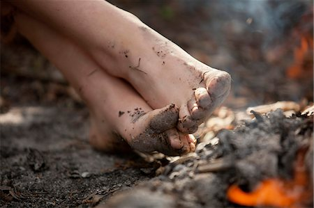 Low section of a girl with dirty feet in mud Stock Photo - Premium Royalty-Free, Code: 698-06374669