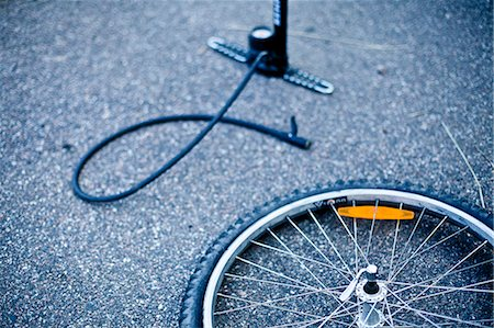 Bicycle wheel and pump lying on road Stock Photo - Premium Royalty-Free, Code: 698-06374684