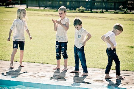 Full length of four children standing by swimming pool Stock Photo - Premium Royalty-Free, Code: 698-06374683