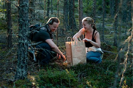 selecting - Mid adult couple foraging for mushrooms in woods Stock Photo - Premium Royalty-Free, Code: 698-06374745