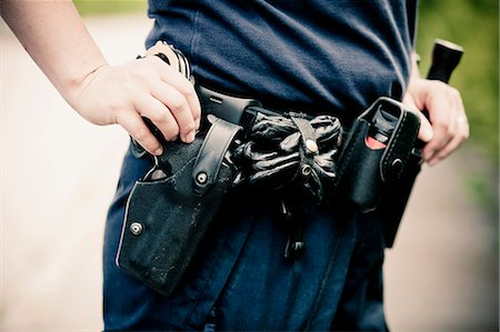 Midsection of a police officer wearing equipment belt Stock Photo - Premium Royalty-Free, Code: 698-06374909