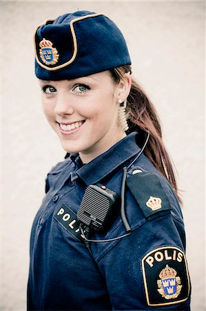 female police officer happy - Portrait of a happy young female police officer Stock Photo - Premium Royalty-Free, Code: 698-06374917