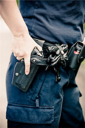 Midsection of a police officer wearing equipment belt with hand on gun Stock Photo - Premium Royalty-Free, Code: 698-06374910