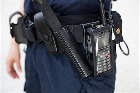 Midsection of a police officer with walkie-talkie and night stick on equipment belt Stock Photo - Premium Royalty-Free, Code: 698-06374928