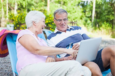 Happy senior couple shopping online together while relaxing on lounge chairs Stock Photo - Premium Royalty-Free, Code: 698-06374963